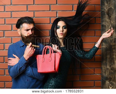 serious couple of bearded man long beard brutal caucasian hipster with moustache and pretty woman or sexy girl with brunette hair makeup in green sequins dress hold bag and cigar on brick wall