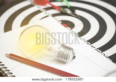 lightbulb on paper book and dartboard with arrow. concept for new ideas with innovation and creativity.
