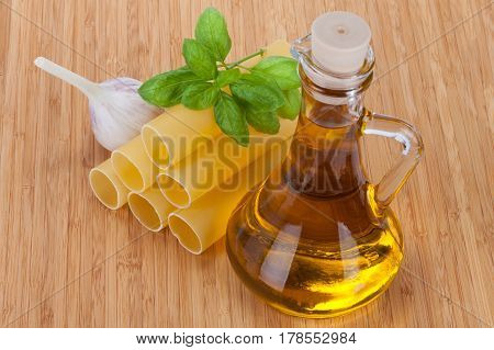 Cannelloni With Olive Oil In A Glass Bottle, Fresh Basil And Garlic Isolated On Wooden Table