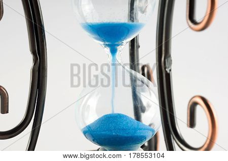 Vintage Hourglass With Curls Patterns On The Edges. Presuposes (perespevshie) Blue Sand In Them.