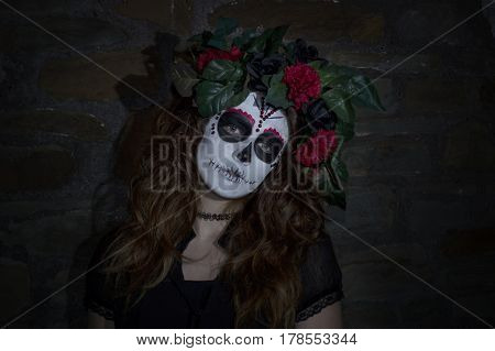 Portrait image of an attractive young woman dressed in a Mexican day of the dead inspired costume. taken with a brick wall background