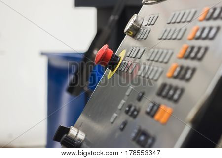 Red button of control panel machine processing of metal, industrial background, close up