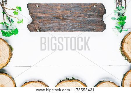 Background of wood planks painted in white. Bunches of blooming apple tree and young black current twigs in upper corners and apple tree slices on edge. Wood sign board as title bar