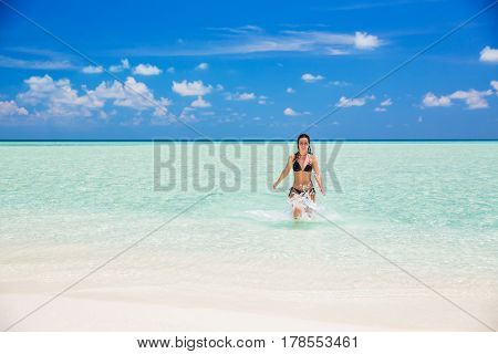 Attractive young woman enjoys Maldivian beach running in the ocean water