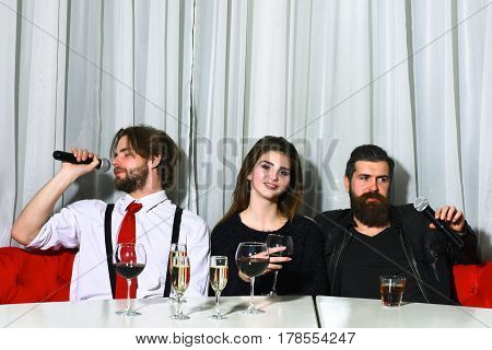 Friends celebrating at karaoke party on white curtain. Two bearded men hipsters with beards holding microphones for pretty girl or beautiful woman for singing