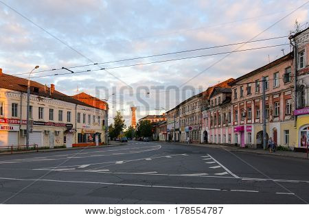 RYBINSK RUSSIA - JULY 21 2016: Unidentified people are walking on Stoyalaya Street in small provincial Russian town Rybinsk in sunset. Far away fire tower (architectural monument of federal significance was built in 1912 by architect I.K. Hotin)
