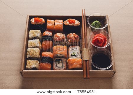 Sushi delivery, restaurant take away in craft carton, maki gunkan roll plate or platter set. Chopsticks, ginger, soy sauce, wasabi. Meals in delivery box