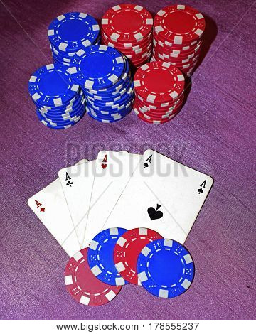 Four aces lie on a purple background with red and blue chips