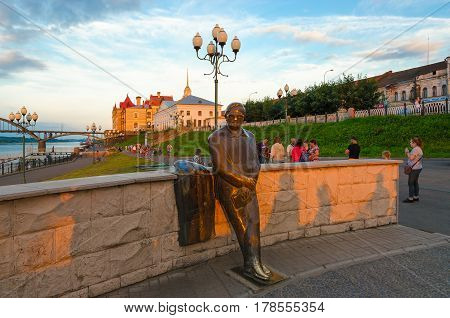 RYBINSK RUSSIA - JULY 21 2016: Unidentified people are walking near monument to Lev Oshanin on promenade in small provincial Russian town Rybinsk on sunset