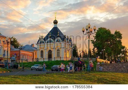 RYBINSK RUSSIA - JULY 21 2016: Unidentified people are walking near Chapel of St. Nicholas Wonderworker on Volzhskaya promenade in small provincial Russian town Rybinsk in sunset