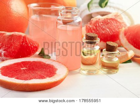 Bottles of grapefruit juicy essential oil. Fresh sweet citrus fruit slices with vials of extract. Aromatherapy treatment.