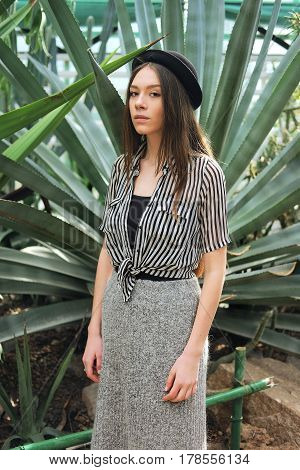 Young fashionable caucasian woman with long hair wearing hat and striped blouse basking in sunlight inside greenhouse near agave plants
