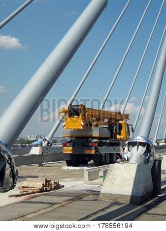 construction of a bridge with a main pillar with wires and a large crane