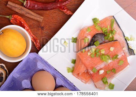 Fresh Salmon Fillet On White Plate. Red Pepper, Cinnamon And Lemon