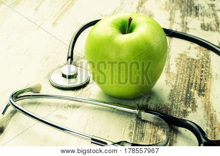 Good health. Green apple with medical stethoscope.