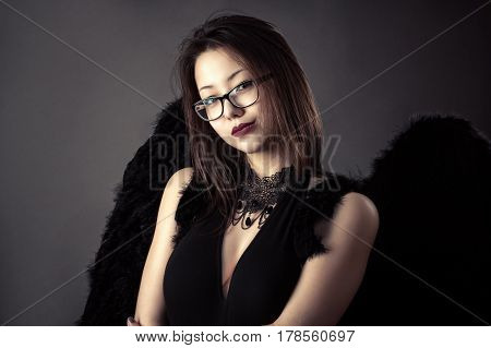 young Korean girl with black wings in studio