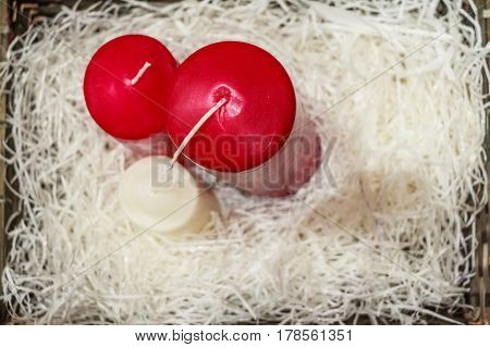 Top view on red and white unlit candles on white fluffy background