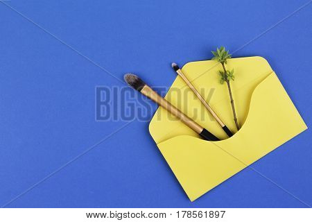 Make up brushes with first spring gentle leaves and buds on small tree twigs in yellow envelope on blue background