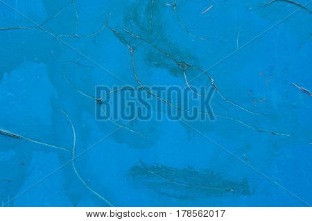 Closeup of old grunge cement wall painted blue with cracks in paint