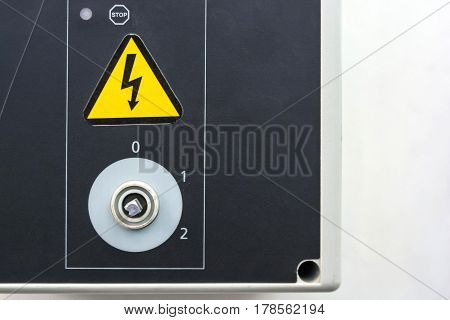 Close up of metal door of electrical panel with broken knob and yellow high voltage sign
