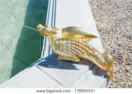 A gilded water spitting dragon as fountain decoration in The Loo park in Apeldoorn Netherlands.