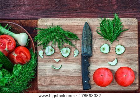Fresh tomatoes and cucumber in a bowl and on a kitchen board funny faces males and women from pieces of cucumber and a bunch of dill top view