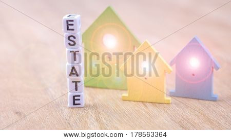 ESTATE word of cube letters behind coloured house symbols with light flares in windows on wooden surface. Concept