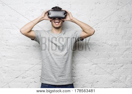 Astonished caucasian male in gray t-shirt using oculus rift headset experiencing virtual reality while playing video game holding hands on goggles looking joyful standing against white brick wall