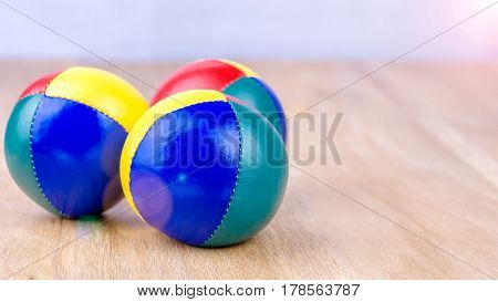 Multi-Coloured juggle balls on wooden surface. Bright light