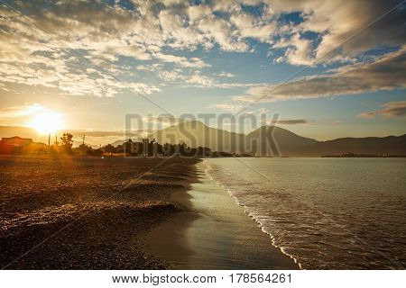 Landscape sea shore in sunshine on the background of mountains and sunset sky
