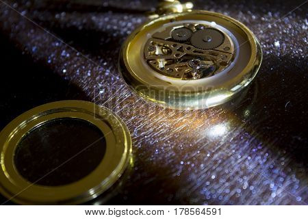 old pocket watch illumined from crossed light