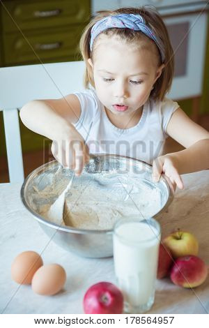 Children Cooking Happiness Kid Home Concept. Girl stir the dough