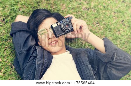 Asian guy lay down and takes photo with camera