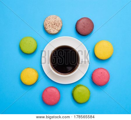 A cup of aroma coffee encircled with a delicious homemade macaroons
