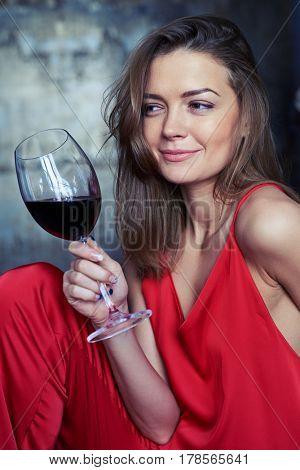 Side view shot of an elated Caucasian girl with a glass of red wine looking sideward. Pretty female holding a glass of red wine in hand. Looking sideward