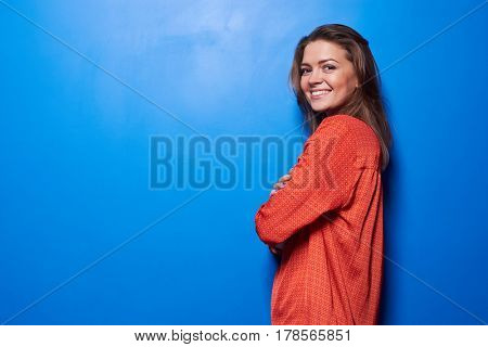 Half-turned portrait of an exhilarated young female standing against blue background. Studio shot of pretty girl isolated