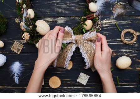 Hand tying bow on a handmade Easter wreath, flat lay composition. Woman making a festive wreath