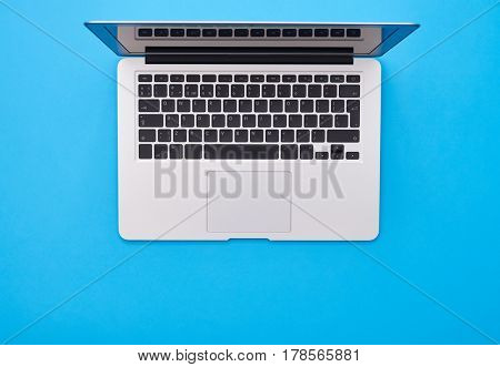 High angle shot of an open silver laptop lying on the blue flatlay. Modern silver laptop with English keyboard isolated. Place for copy space