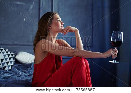 Side view of a thoughtful female holding hand near chin and looking far. Wearing a red overall, resting at home. Dreamy girl spending time indoors