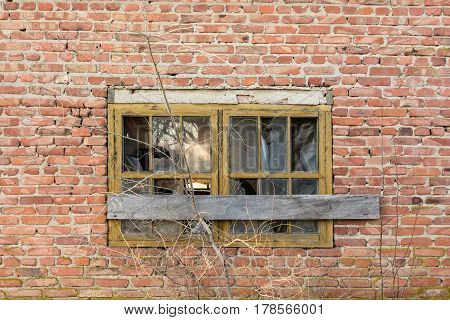Obsolete demolished boaded up window on red brick wall