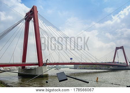 Rotterdam Netherlands - May 26 2016: The bridge Willemsbrug spans the river Nieuwe Maas with along the embankment modern art