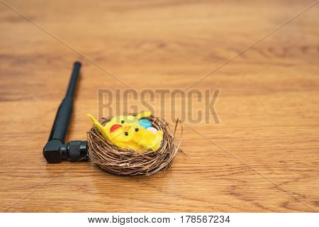 A small antenna connected to the nest with chickens and Easter eggs, lies on a wooden table