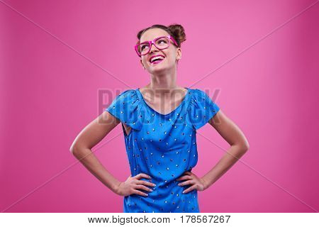 Mid shot of good-looking girl in dotted blue dress with hands on hips looking upwards. Elated girl broadly smiling posing over pink background