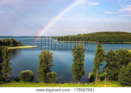 Rainbow in summer over the Stroust lake in Braslav region of Belarus.