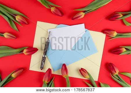 Blank card, pen, blue envelope and red spring tulips flowers on red background. Top view. Flat lay