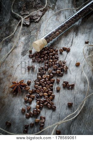 Bean Coffee In A Glass Vial On Aged Wood