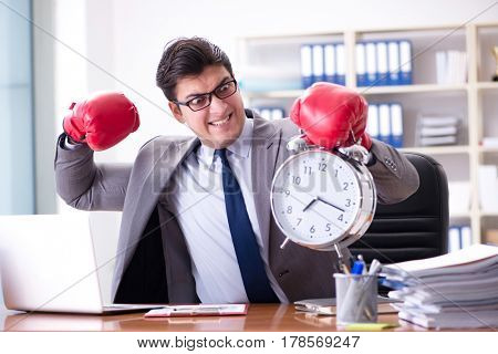 Angry businessman with boxing gloves in time management concept