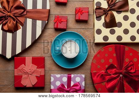 Photo Of Cup Of Coffee Near Different Colorful Gifts On The Wonderful Brown Wooden Background