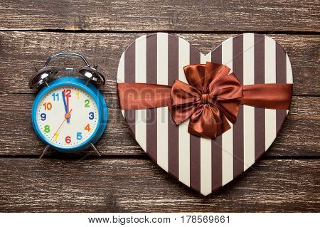 Photo Of Cute Wrapped Gift And Alarm Clock On The Wonderful Brown Wooden Background