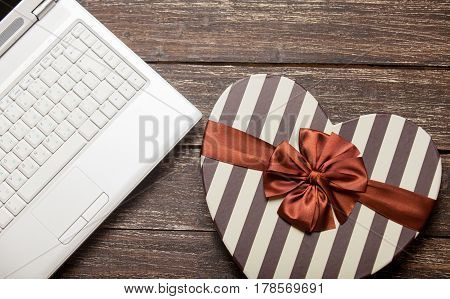 photo of cute wrapped gift and laptop on the wonderful brown wooden background